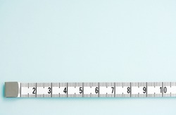 Close up detail view of a measuring tape stretched in a straight line isolated on a clean blue background.