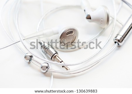 Close up detail view of a pair of musical earphones laying together with cable around them, isolated on a white background.