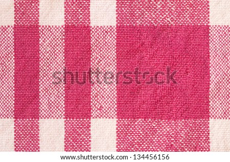 Close up detail view of a patterned cotton kitchen cloth with visible weave and bright color checks.