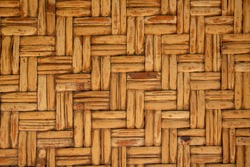 Close up detail view of a wicker basket weave with natural materials. Natural wooden background