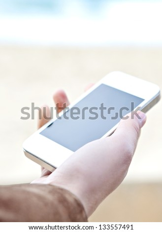 Close up detail view of a woman's hand holding a modern smart phone with a blank screen against a neutral background and the sea.
