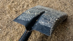 Close up detail view of dirty shovel on the ground. It is a hand tool for digging, lifting, and moving bulk materials, such as soil, coal, gravel, snow, sand, or ore.