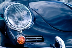 Close-up, detailed photo of the front, grille and head lamp of a classic oldtimer car.