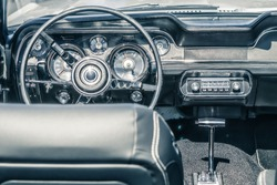 Close-up, detailed photo of the interior, dashboard, steering wheel and speedometer of a classic oldtimer american muscle car.