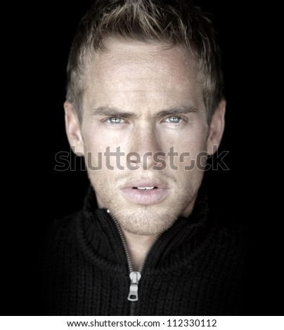 Close-up detailed portrait of young good looking male model against black background