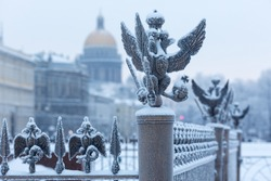 Close up details fence decorations with the Russian imperial double-headed eagle symbol covered with snow on Palace Square, St. Petersburg, Russia