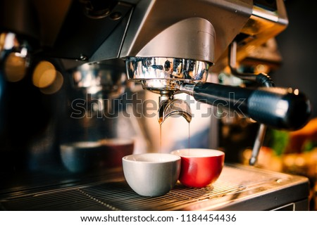 Close up details of brewing machinery pouring and preparing espresso in two cups. Cafe shop details