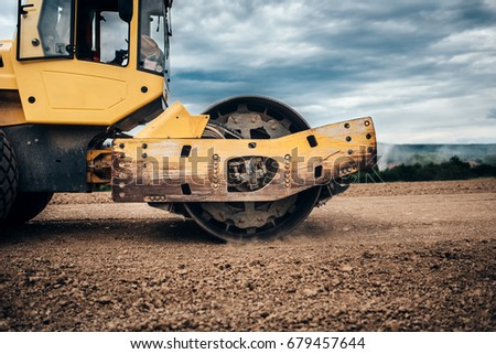 Close up details of industrial road soil compactor, vibratory roller and heavy duty machinery during highway construction