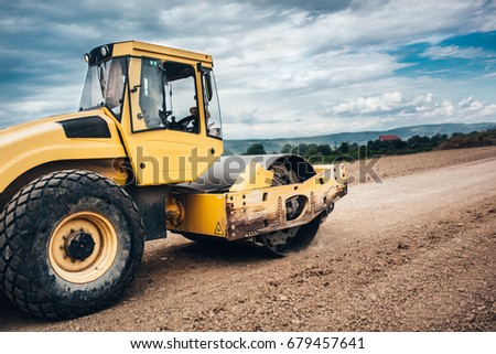 Close up details of industrial roadworks with tandem roller and vibratory soil compactor