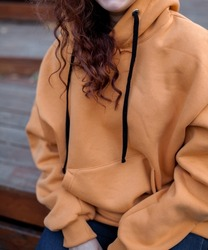 close up details of oversized orange color hoodie  at female.fashion and wear concept. warm oversize wear at woman.space for text and logo.close up details of oversize wear.close up