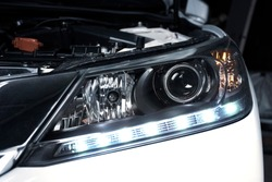 Close up details of projector lens headlights and daytime running light technology in a car.