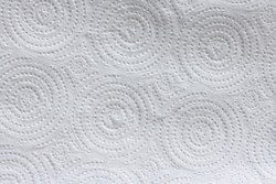 Close up details of white paper towel with circular pressed dot pattern. Everyday household item environmental concept.