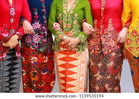 Close up details shot of southeast Asian woman in traditional Malay batik kebaya dress.