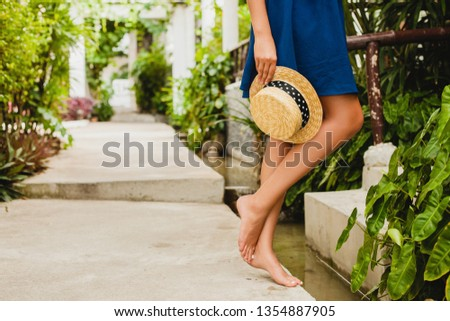 close up details skinny leg of sexy slim young woman in blue dress holding straw hat walking barefoot at tropical spa villa hotel on vacation in summer style outfit