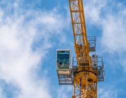 Close up details with a cabin control of a construction crane.Turret Slewing Crane against blue sky