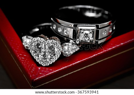 Close up diamond couple wedding rings on luxury red box #367593941