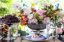 Close up dinner tableware set that has flowers and fruits decoration as food ingredient at home.