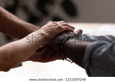 Close up diverse male female sitting holding hands together. Multiracial people starting common business or celebrate success at work stacked hands together showing unity support, all for one concept