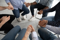 Close up diverse people sitting on chairs in circle at group training counselling session, holding hands, psychological help and treatment concept, drug or alcohol addiction rehabilitation