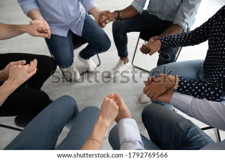 Close up diverse people sitting on chairs in circle at group training counselling session, holding hands, psychological help and treatment concept, drug or alcohol addiction rehabilitation Stock photo ©