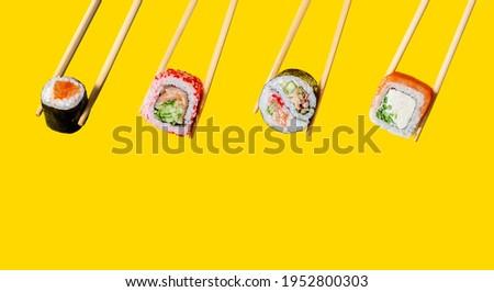 Close up Diversity Rolls. Maki, California, Yin-Yang and Philadelphia on chopsticks on yellow background