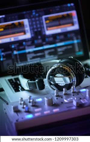 Close up DJ computer workstation controller desk for live performance. Stereo headphones earphones space set indoors, colorful lights at dark room. Audio program on laptop computer screen, nobody #1209997303