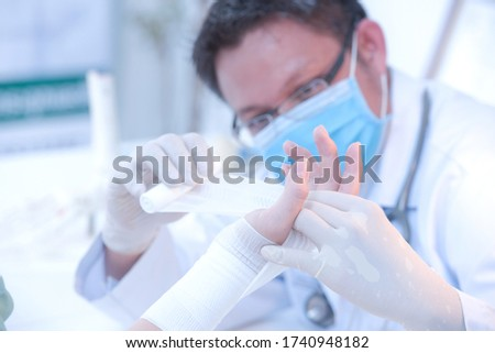 Close-up doctor is bandaging upper limb of patientFirst aid and treatment in wrist injuries and disorders Foto stock ©