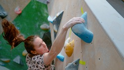 CLOSE UP, DOF: Athletic Caucasian woman climbing indoors reaches the top hold of a challenging boulder route. Action shot of a chalk covered hold as the young female climber tops artificial boulder.
