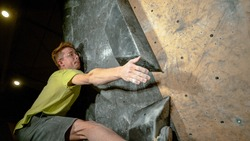CLOSE UP, DOF: Caucasian climber wearing glasses reaches up to grip a hold while training in an indoor boulder climbing center. Athletic young man grabs a black volume hold while climbing indoors.