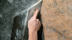 CLOSE UP, DOF: Climber uses a brush to scrub excess chalk powder off a black volume hold. Unrecognizable man brushes a layer of magnesium off a climbing grip at an indoor gym during maintenance work.