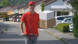 CLOSE UP, DOF: Content young courier rides his e-scooter down the empty suburban street with two packages. Parcel delivery man skilfully holds two boxes in one hand while riding an electric scooter.