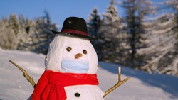 CLOSE UP, DOF: Funny looking snowman wearing a black hat wears a surgical mask to protect him from the coronavirus. Snowman standing in wintry countryside obeys covid19 protocols by wearing a facemask