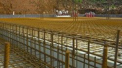 CLOSE UP, DOF: Ground floor of a modern house under construction waits for concrete slab pouring. Rusty metal wiring is laid on the ground of house under construction. Reinforced basement floor.