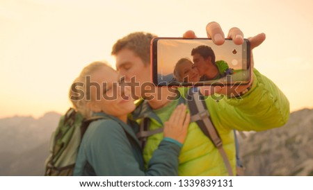 CLOSE UP, DOF: Happy Caucasian man takes a selfie of him kissing girlfriend on the cheek on a sunny summer evening after reaching the mountaintop in the breathtaking Alps. Hiker couple taking photos.