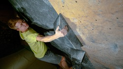 CLOSE UP, DOF: Nimble young Caucasian man climbs up a challenging route at a dark climbing gym. Focused male climber grips a rough black volume hold while training at an indoor bouldering facility.