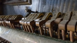 CLOSE UP, DOF: Old broken dusty piano from the inside. Hammers in abandoned piano striking strings tuned to produce the note when a piano key is pressed. Music playing from the ancient ruined piano