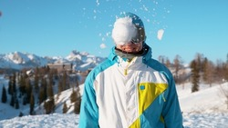 CLOSE UP, DOF: Stoked male snowboarder gets hit in the head by a large wet snowball. Cinematic shot of a happy young male tourist wearing goggles getting hit by a snowball during a random snowfight.