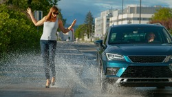 CLOSE UP, DOF: Thoughtless senior driver drives her metallic blue car into a puddle, splashing water at the young female pedestrian walking along the empty sidewalk in her brand new high heels.