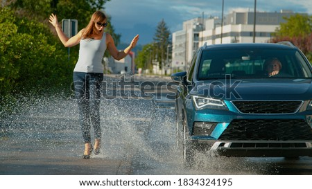 CLOSE UP, DOF: Thoughtless senior driver drives her metallic blue car into a puddle, splashing water at the young female pedestrian walking along the empty sidewalk in her brand new high heels. Stock photo ©