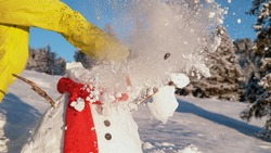 CLOSE UP, DOF: Unknown person blowing off steam kicks a snowman's head off its body. Unrecognizable man wearing bright yellow trousers and winter boots destroying a funny snow man on a sunny day.