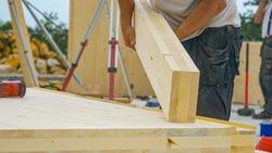 CLOSE UP, DOF: Unrecognizable male builder picks up a CLT beam from a workbench at an unfinished housing project. Contractor carries a glued laminated board across the bustling construction site