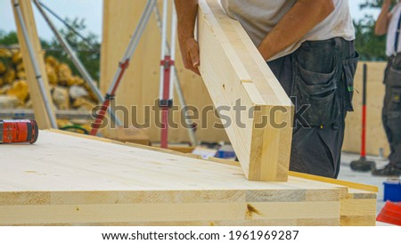 CLOSE UP, DOF: Unrecognizable male builder picks up a CLT beam from a workbench at an unfinished housing project. Contractor carries a glued laminated board across the bustling construction site ストックフォト ©