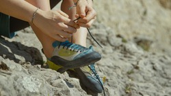 CLOSE UP, DOF: Unrecognizable woman ties her climbing shoes before climbing a difficult boulder. Athletic woman on rock climbing trip gets ready for her first ascent by tying her climbing shoes.