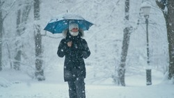 CLOSE UP, DOF: Young Caucasian woman looks around the idyllic wintry park during a severe blizzard engulfing Ljubljana. Carefree female pedestrian walks along snowy avenue on a cold Christmas day.