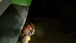 CLOSE UP, DOF: Young male climber wearing glasses reaches up to grab a black volume hold at the top of the climbing route at a dark indoor facility. Man climbs to the top of an artificial boulder.