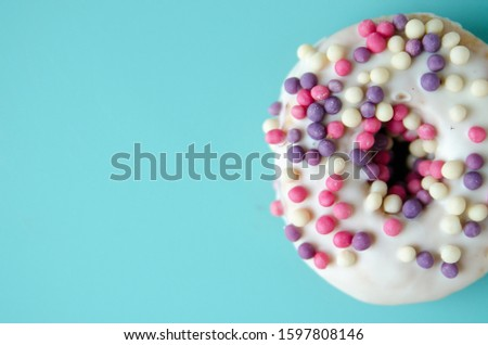 Close up donut with colorful sprinkles on pastel blue background. Wallpaper for smartphone