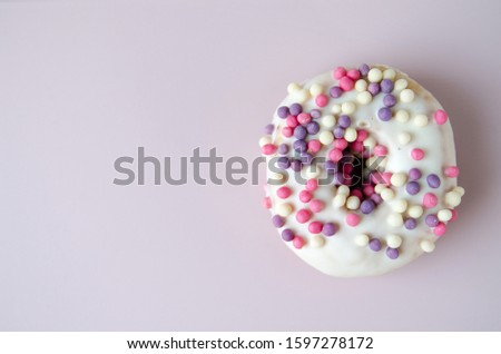 Close up donut with colorful sprinkles on pastel pink background. Wallpaper for smartphone