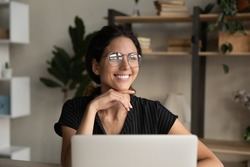 Close up dreamy smiling businesswoman in glasses distracted from laptop, looking to aside, pensive young woman visualizing good future, dreaming about new opportunities, pondering project strategy