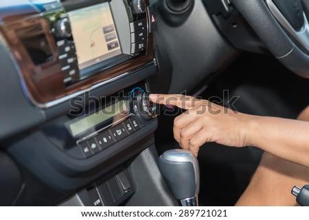 Close up driver hand press air-con button in the car