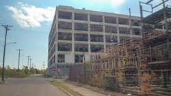 CLOSE UP: Driving towards the ruin of derelict dilapidating Fisher Auto Body Plant 21 in decaying Detroit, United States. The remains of broken down and destroyed car factory in desolate cityscape
